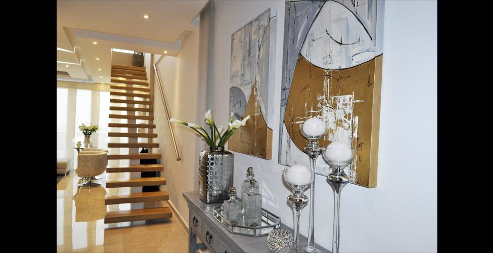 velas y flores frescas dan la bienvenida a este apartamento un par de cuadros de guiselle borrs el mueble gris diseado por vivian feris